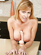 Busty Anilos Nicole Moore strips off her clothes and sucks on a thick dildo