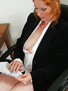 Redheaded Rose plays around with her furry pussy on workplace